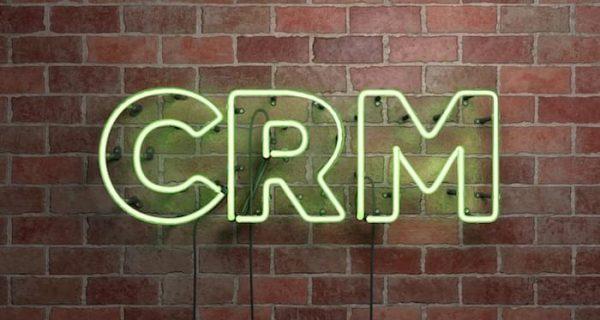 CRM - fluorescent Neon tube Sign on brickwork