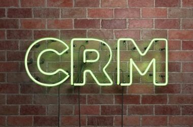 CRM - fluorescent Neon tube Sign on brickwork